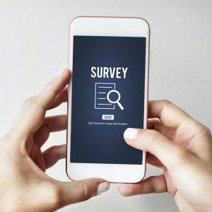 two hands holding a mobile phone that says survey on the screen