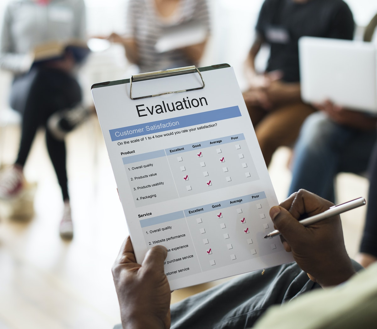 person holding a clipboard with a checklist on it that says evaluation