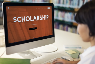 Person sitting in front of a computer monitor that says Scholarship on it